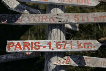 pices: Old wooden signpost on roadmap shows which way and how much left to Paris and New Yourk. It is very old and left on the ground even it has some broken pices but it looks amazing and vintage.