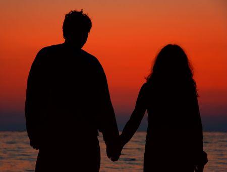 curare teneramente: Giovane coppia in spiaggia al mattino  Archivio Fotografico