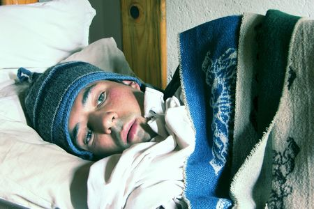 Young person in a bed feeling cold photo