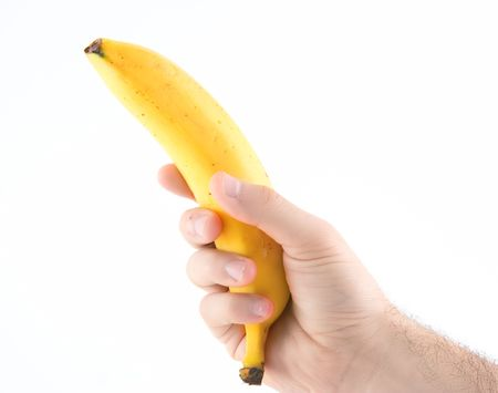 A hand holding a banana against white background photo