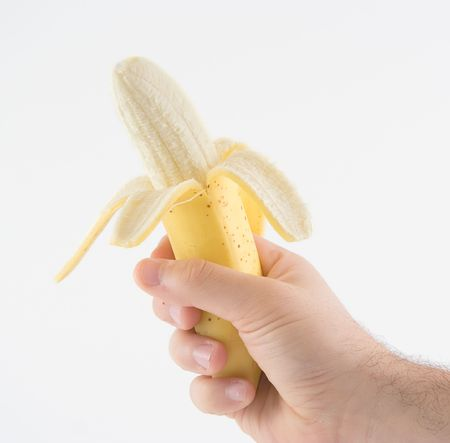 A hand holding a peeled banana against white background photo