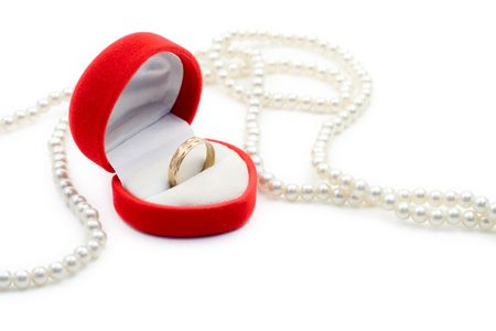 Pearls and a golden ring against white background photo