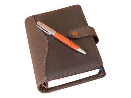 memorize: Closed notebook and a pen on it against white background