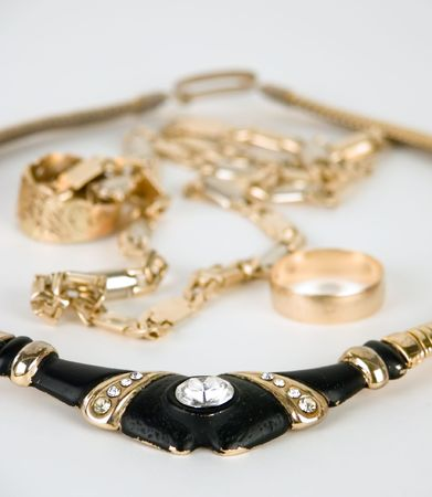 frippery: Necklace and golden chain against white background