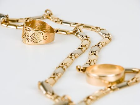 frippery: Golden chain and ring against white background