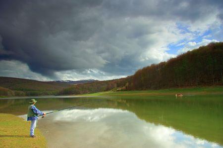 macedonia: Fisherman catching fish on a lake in Macedonia Stock Photo