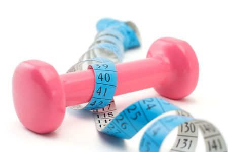 measurement tape: Women�s weights wrapped around a measurement tape Stock Photo