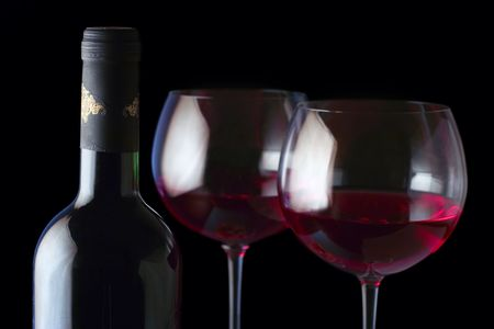 Wine bottle and two glasses against black background