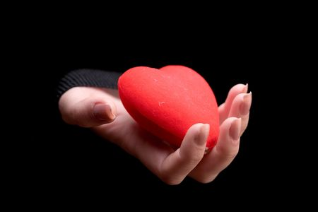 Woman�s hand holding a red heart against black background