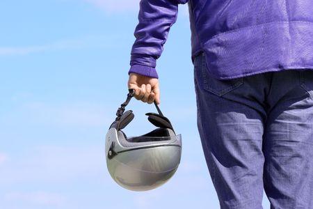 Biker holding a helmet against blue sky photo