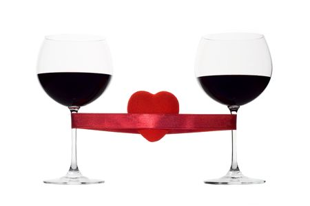Two wine glasses tied with a red heart against white background photo