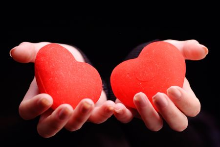 soul mate: Woman holding two red hearts against black background