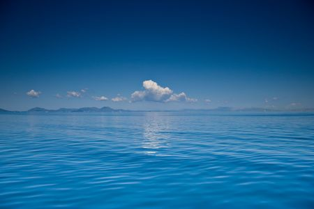 View of an open sea with a cloud on Corfu island, Greece photo