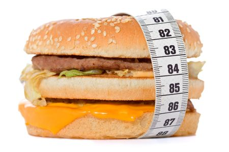 Hamburger wrapped around a measurement tape against white background Stock Photo - 551499