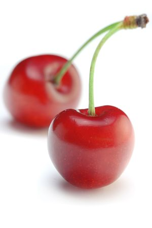 Two cherries against white background