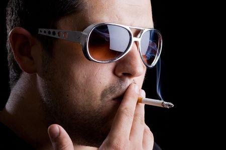 Handsome model smoking a cigarette against black background photo