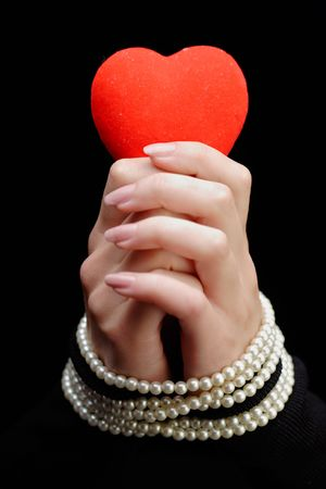 Woman holding a red heart with her hands tied with pearls photo