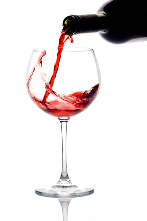 Red wine pouring down from a wine bottle against white background photo