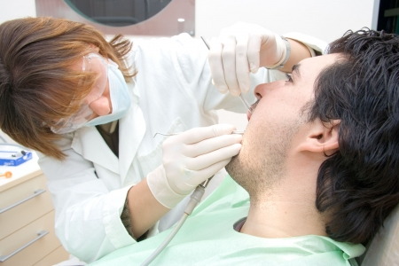 Female dentist examining a male patient