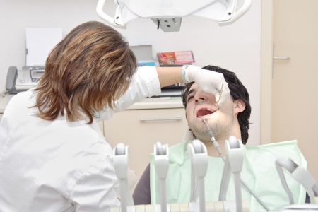 Female dentist examining a patient photo