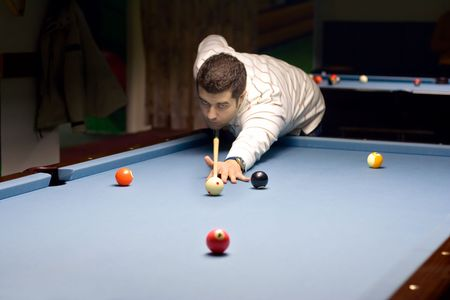 Young person playing snooker in a club photo