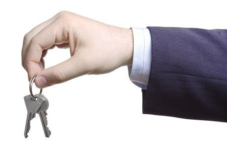 Hand holding two keys against white background