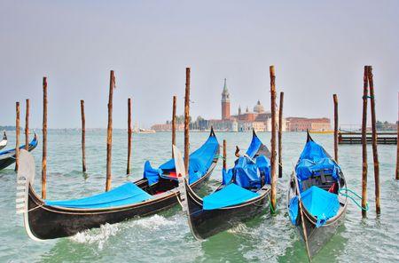 Gondola moored at Molo San Marco in Venice, Italy with San Giorgio Maggiore basilica in the background photo