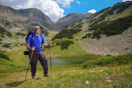 Hiker climbing a peak at national park Pirin, Bulgaria with Prevalski ezera and  Mozgoviska porta in the background Stock Photo - 1406358