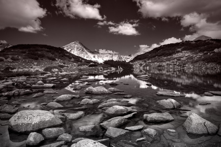 Glacial lake Zabecko with Hvoinat peak at national park Pirin, Bulgaria in black and white photo