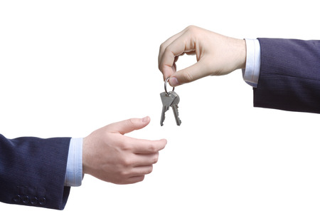 Person passing door keys against white background Stock Photo - 1716519