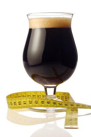 Dark beer with a measurement tape wrapped around it photo