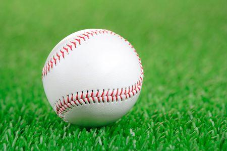hardball: Baseball ball on a green grass background Stock Photo