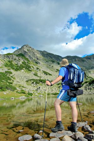 Hiker at Prevalski lake in national park Pirin, Bulgaria photo