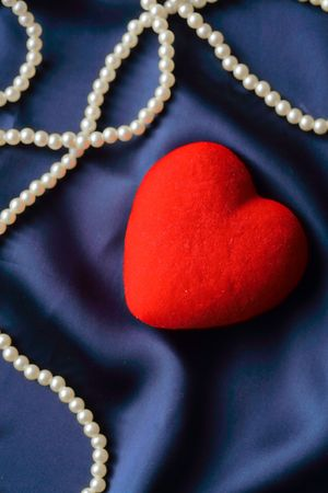 Pearls and red heart on a satin background photo