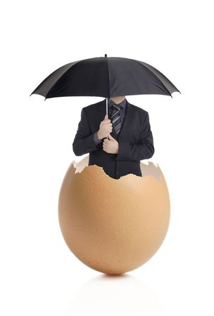 Man with an umbrella hatching out of an eggshell  photo