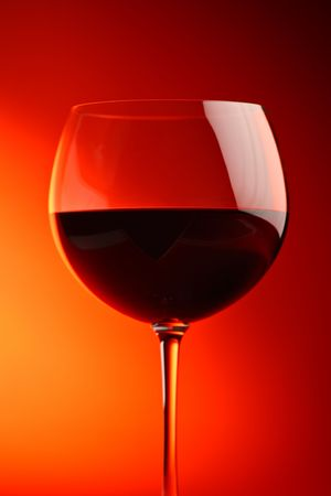 Wine glass against red background photo