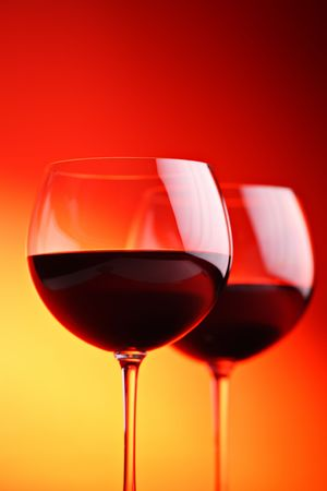 Wine glasses against red background photo
