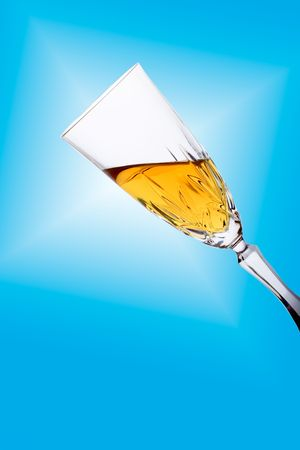 Glass filled with white wine (clipping path included) against blue background photo