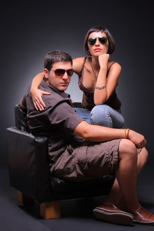 Young couple posing in a studio against black background photo