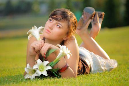 sensing: Attractive girl lying on the grass sensing flower Stock Photo