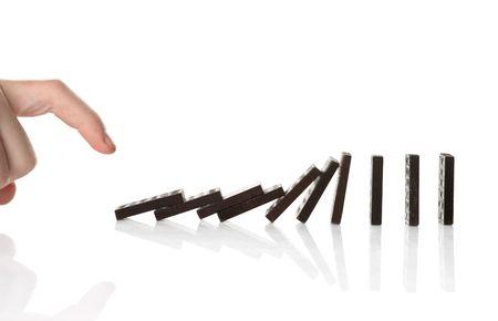 causing: Hand pushing dominoes causing chain reaction Stock Photo