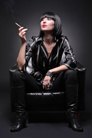 Fashionable young woman sitting in an armchair having a cigarette Stock Photo
