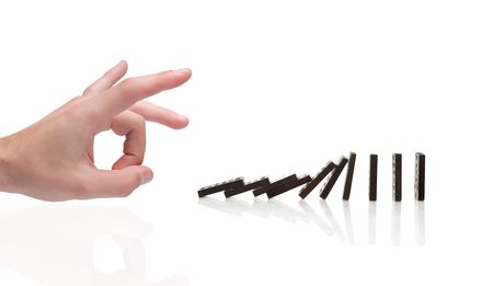 domino effect: Person pushing domino blocks isolated against white background Stock Photo