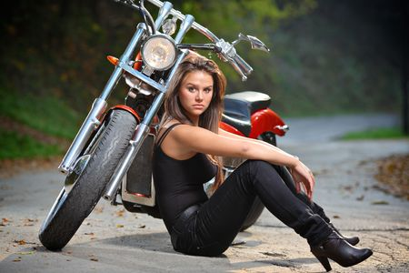 Biker girl sitting next to a bike photo