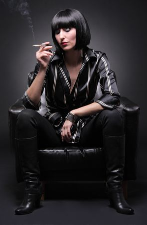 Fashionable young woman sitting in an armchair having a cigarette photo