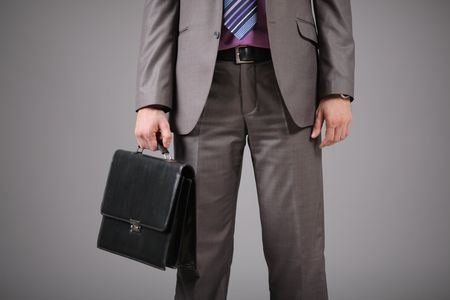Businessman holding a briefcase against grey background photo