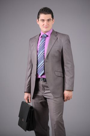 Businessman with a briefcase against grey background Stock Photo - 4002832