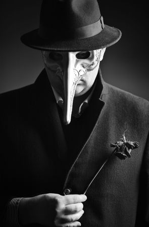 A black-and-white portrait of a man with a Venetian carnival mask Stock Photo