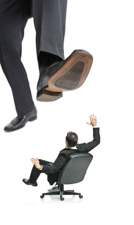 A giant foot about to squish a businessman in a chair isolated on a white background photo