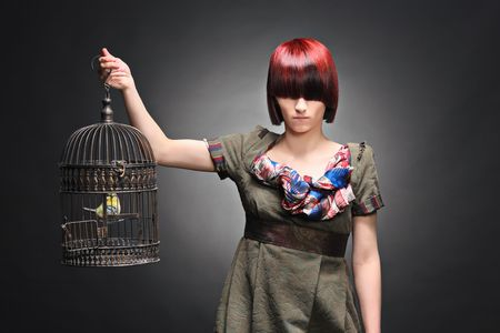 A beautiful young girl holding a birdcage isolated on a black background photo